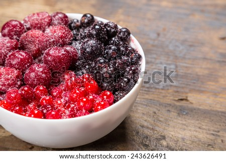frozen berries in white plate on wooden background - stock photo