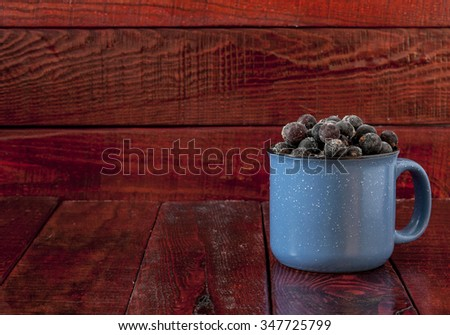 frozen black currant in the mug on a wooden background - stock photo