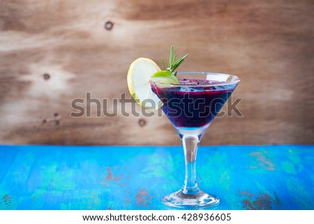 Frozen black currant margarita cocktail in a martini glass, refreshing summer drink - stock photo