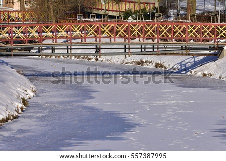frozen brook with small bridge
