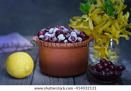 Frozen cherries in a ceramic pot, cherry jam and lemon.Beavertail gray-blue background, rustic style - stock photo