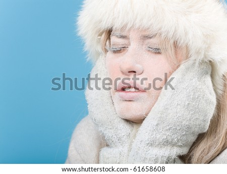 Frozen. Close-up portrait of chilled female face covered in snow ice. - stock photo
