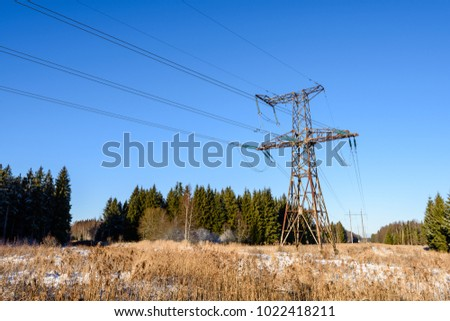 frozen country side by the forest with power lines and blue sky