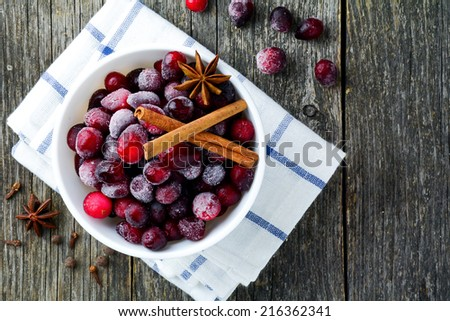 Frozen cranberries in white bowl with spices: cinnamon stick, star anise and cloves on rustic wooden table top, above - stock photo