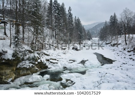 Frozen fast mountain Prut river in winter. Spring melting of ice, springtime thaw. Yaremche, Ukraine.