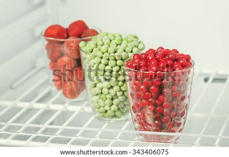 Frozen food in the freezer, red currants, strawberries and green peas - stock photo