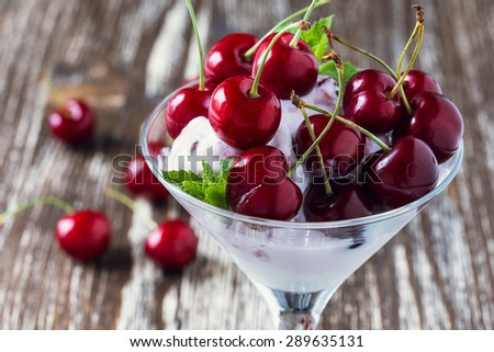 Frozen fruit soft ice cream dessert with sweet cherry on top in martini glass on shabby chic background - stock photo