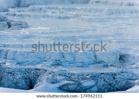 Frozen geyser bacteria pattern with hot water flowing over it - stock photo