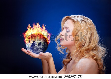 Frozen girl holding burning earth globe (east hemisphere) in palms (elements furnished by NASA) - version with glowing - stock photo
