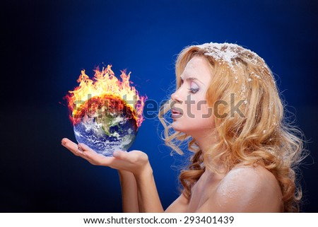 Frozen girl holding burning earth globe (west hemisphere) in palms (elements furnished by NASA) - version with glowing - stock photo