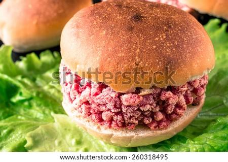 Frozen hamburger ground beef on lettuce - stock photo