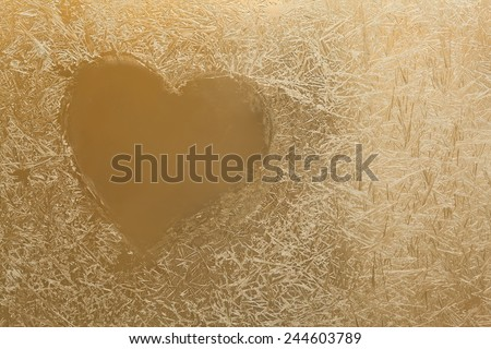 Frozen heart. Frozen glass. Ice flowers. Frost flowers. Window frost. Winter window. Frozen window. Valentines day background. (Macro. Soft focus. Toned photo). - stock photo