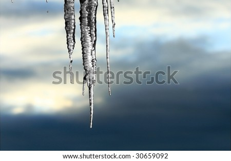 Frozen icicles against an ominous sky. - stock photo