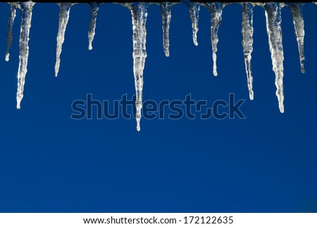 Frozen icicles hanging from a roof isolated against a blue sky background - stock photo