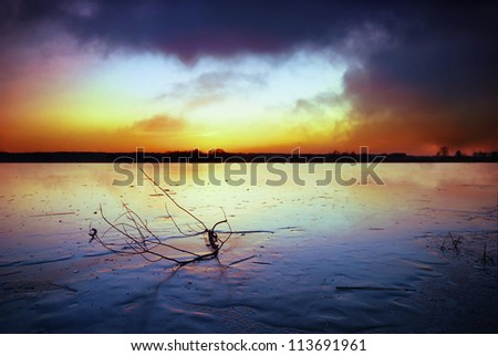 Frozen lake and dark clouds at sunset