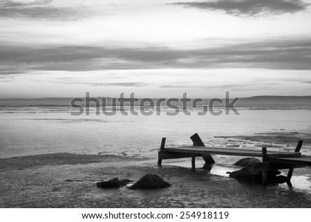 Frozen lake and mole,dawn with  clouds,black and white photo - stock photo