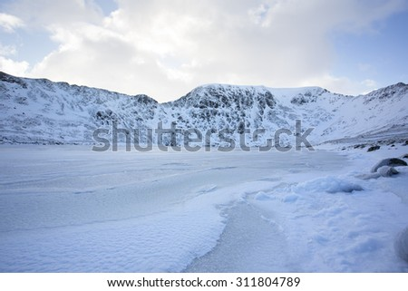 frozen lake and snow covered mountains, helvellyn, cumbria - stock photo