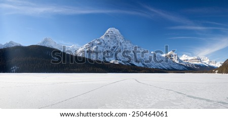 Frozen Lake and Snow Mountain in Canadian Rockies - stock photo