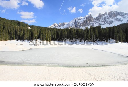 frozen Lake Carezza and the Italian alps Dolomites during winter, unesco world heritage, Italy - stock photo
