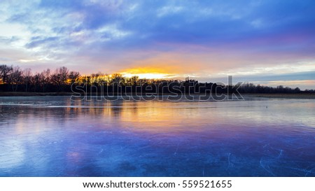 Frozen lake in Europe in Hungary, reflecting the ice beautiful colorful clouds.