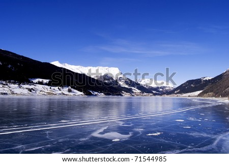 frozen lake in winter with the Alpine mountains and blue sky - stock photo