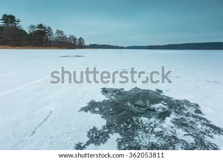 Frozen lake landscape with hole in ice for ice fishing. Beautiful lake in Poland. - stock photo