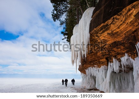 Frozen Lake Superior shoreline.  Orange cliff, large icicles, people for scale.  Copy space.  Apostle Islands National Lakeshore on Lake Superior.  Popular winter travel destination. - stock photo