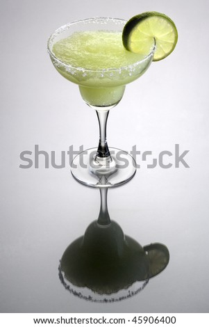 Frozen Margarita mixed drink with lime slice garnish on plain grey background with reflection - stock photo