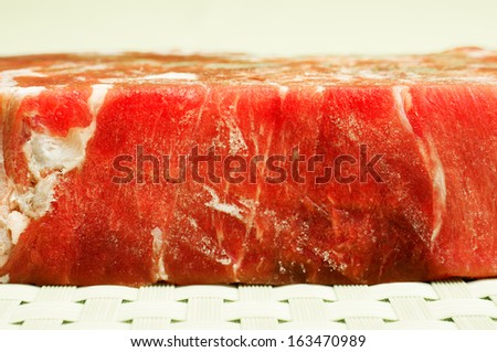 Frozen meat. Frozen beef melts on a green background. - stock photo