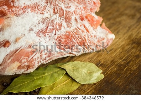Frozen meat on a wooden table - stock photo