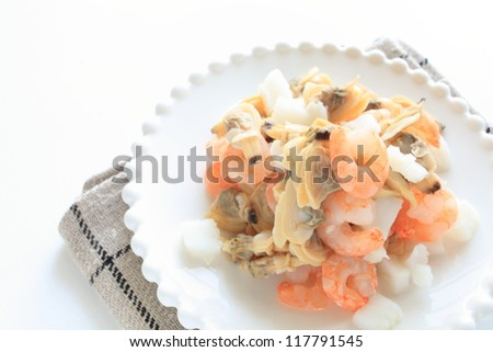 frozen mixed seafood on white dish with copy space - stock photo