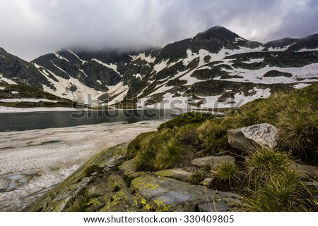 Frozen mountain lake, Rila mountain, Bulgaria - stock photo