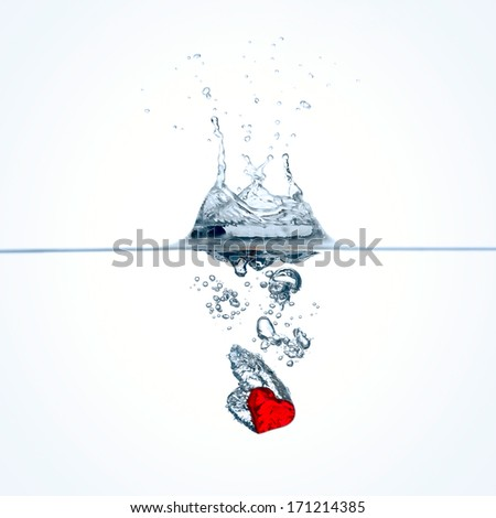 Frozen movement of red heart falling into water