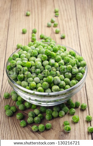 Frozen peas in a glass bowl on a wooden table - stock photo