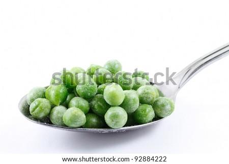 Frozen peas on a spoon - stock photo
