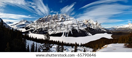 Frozen Peyto Lake Panorama in Winter Unlike in Summer, where it takes on a vivid blue colour, the scene in winter is vastly different.It is a glacier-fed lake located in Banff National Park in Canada - stock photo