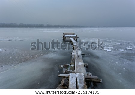 Frozen pier on a winter river. - stock photo