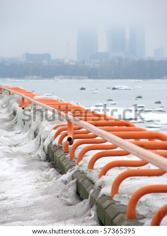 Frozen railings, high-rise buildings on the foggy background - stock photo