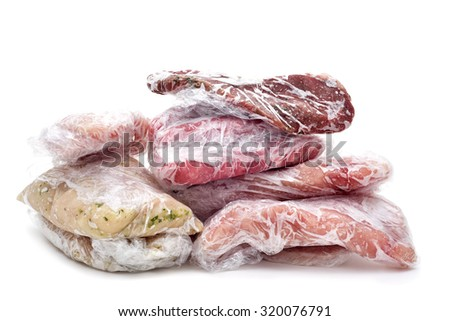 frozen raw meat, such as pork, chicken or beef, wrapped in plastic on a white background - stock photo