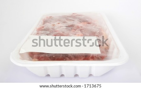 Frozen raw supermarket meat on white, isolated, copy space, close-up, macro. - stock photo