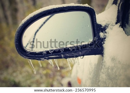 Frozen rearview mirror of the car with icicles, ice and frost - stock photo
