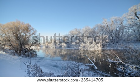 Frozen river and trees at winter sunny day. - stock photo