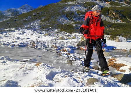 Frozen river on the mountain and woman climber walking across it  - stock photo