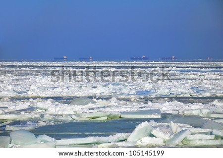 frozen sea with cargo ships - stock photo
