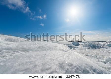 Frozen seashore in winter with sun - Grisslehamn, Sweden - stock photo