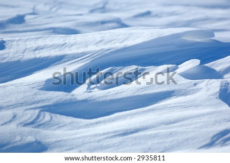 Frozen snow drifts with blue shadows. - stock photo