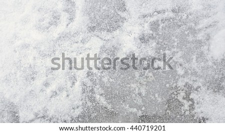 Frozen Snow Ice Texture - Top view texture of surface with grey ice covered in white snow, winter icy ground background photo. - stock photo