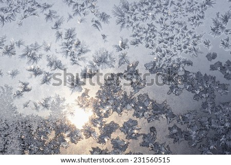 Frozen snowflakes and frost over the sun on frozen Christmas winter window. Colored in gray or silver tone. Selective focus at center with blur edges of image - stock photo