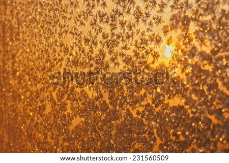 Frozen snowflakes and frost over the sun on frozen Christmas winter window. Colored in yellow or gold tone. Selective focus at center with blur edges of image - stock photo