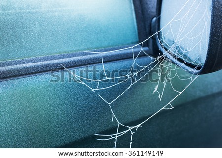 frozen spider web covered with frost early in the morning on side view mirror of a car, winter time, cold blue colors, horizontal - stock photo